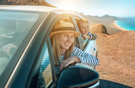 Happiness mother and son, sitting in white car and look ing on the beautiful ocean coastline with mountains. Traveler, Travel, Freedom concept. Banco de Imagens - 132274179