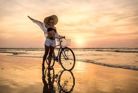 Happiness woman traveler with her bicycle walking on sea coastline and looking on beautifull sunset sky in sunny summer day on beach. Freedom, Travell, Journej,  concept. Reklamní fotografie