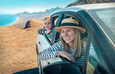 Happiness mother and son, sitting in white car and look ing on the beautiful ocean coastline with mountains. Traveler, Travel, Freedom concept.
