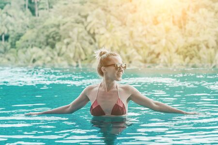 Happiness woman traveler in bikini in water pool near sea coastline  looking on beautifull tropical landscape view in sunny summer day. Freedom, Travell, Journej,  concept. Zdjęcie Seryjne