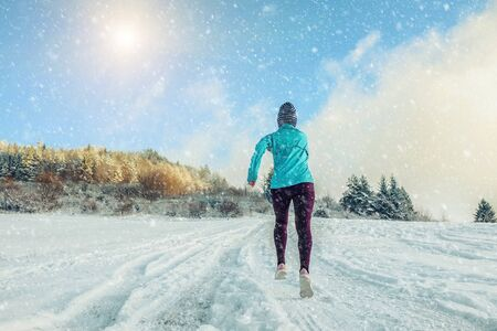 Running woman. Runner on the snow in winter sunny day. Female fitness training outdoors. Zdjęcie Seryjne