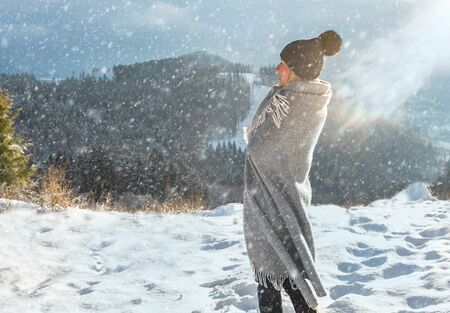 Happy woman traveler on the snowy of mountain looking on the nice winter mountains in sunny day.
