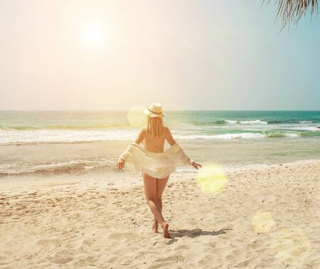 Happy traveller woman in white enjoys her tropical beach vacation in sunny day. Holidays, Travel, Coastline, Freedom concept. Zdjęcie Seryjne