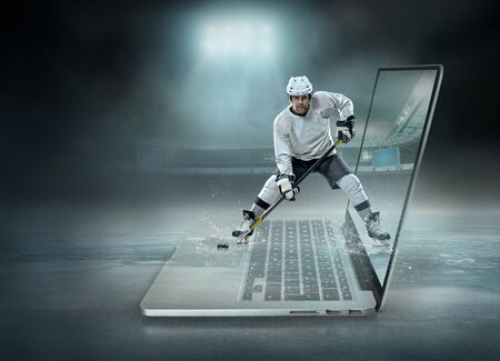 Caucassian ice hockey Players in dynamic action in a professional sport game play on the laptop in hockey under stadium lights. Zdjęcie Seryjne
