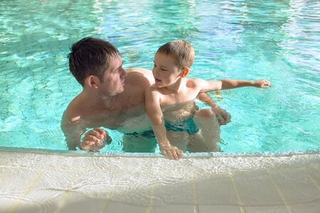 Happy father and son swimming lesson in the pool. Child learning swim. Enjoying summer vacation. Family, parenthood, health, sport concept.