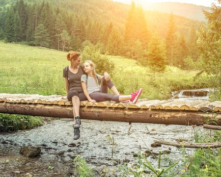 Mother and Douther Hikers with backpacks sitting and relaxing on wooden bridge, enjoying view of sunset sky. Slovakian nature. Traveling along mountains and forest, freedom and active lifestyle concept. Zdjęcie Seryjne