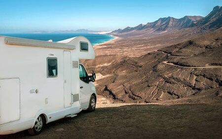White travel caravan car stay on the beautifull ocean coastline with natural view in sunny day. Freedom, Family, Travell, Journej, Travelers concept. Zdjęcie Seryjne