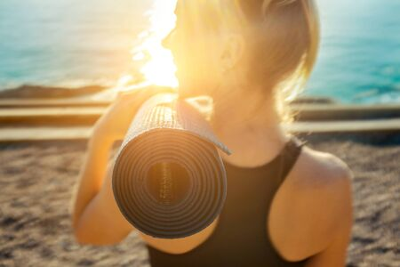 Young woman stay on the sea coastline under sun light at morming time. Yoga concept. Summer fresh air from sea. Zdjęcie Seryjne