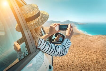Happiness young woman sitting in white car and shoot with her phone camera beautifull ocean coastline view. Freedom, Travell, Journej, Trip, Shooting concept.