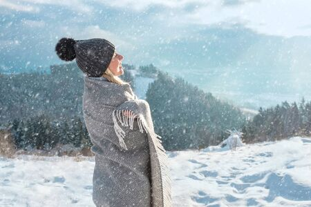 Portrait of Happy woman traveler stay on the snowy land and looking on the nice winter mountains view.