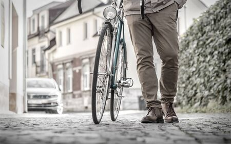 Young stylish businessmango to work on his sport retro bike in sunny day. Zdjęcie Seryjne