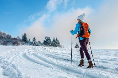 Glücklicher Frauentourist, der auf der schneebedeckten Wanderung auf dem Gipfel des Berges spaziert und am sonnigen kalten Tag die schöne Winteransicht betrachtet. Konzept Reisen und Freiheit. Standard-Bild