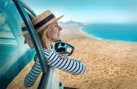 Happiness young woman in hat, sitting in her white car and looking on beautiful ocean coastline view with mountains