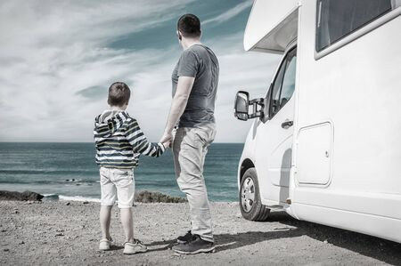 Happiness father and son, stay near them white travel car and look on the beautiful ocean coastline view in sunny day. 写真素材