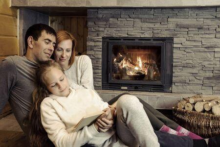 Joyeuse famille de Noël, parents aimants avec une fillette assise près de la cheminée et s'amusant à célébrer des vacances festives en profitant d'un festin à la maison.