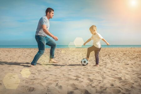 Father and son playing in football on sea coastline beach under sun light in sunny day. Holidays, Sport, Family concept. Archivio Fotografico - 137441223