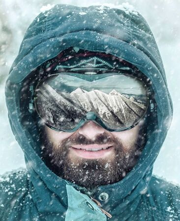 Close-Up Portrait of Caucasian holiday man with beard in winter snow landscape. Beautiful mountains view reflected in ski glasses. Sunny frozen day.