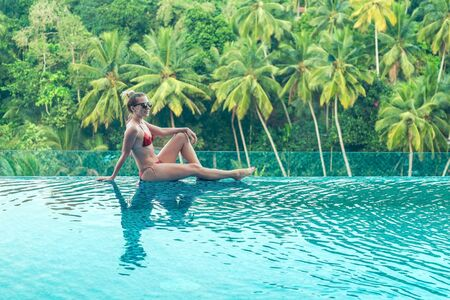 Happiness woman traveler in bikini in water pool near sea coastline looking on beautifull tropical landscape view in sunny summer day. Freedom, Travell, Journej, concept.