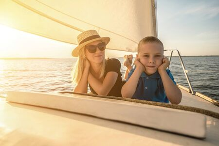 Happy traveler mother and son enjoying sunset from deck of sailing boat moving in sea at evening time. Bonding Travel, Summer, Holidays, Journey, Trip, Lifestyle, Yachting concept. Reklamní fotografie