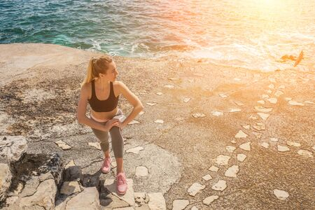 Woman running training on the coastline under sunlight in sunny summer day