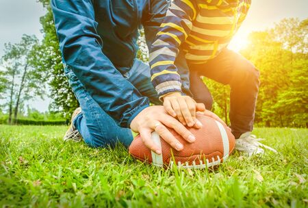 Father and son playing football, Father's day, Playful Man teaching Boy rugby outdoors in sunny day at public park. Family sports weekend. Stock Photo