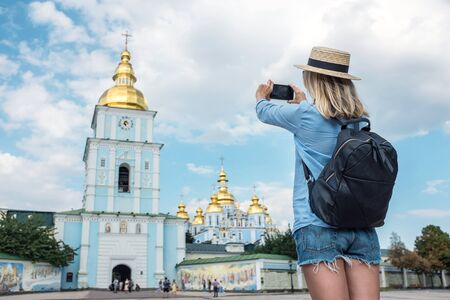 Woman traveler tourist using smartphone, taking photo of church Kiev, Ukraine in summer sunny day. Enjoying European, Famous popular touristic place in world.