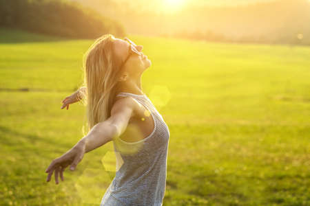 Happy woman with open arms stay on the peak of the mountain cliff edge under sunset light sky enjoying the success, freedom and bright future. Banco de Imagens