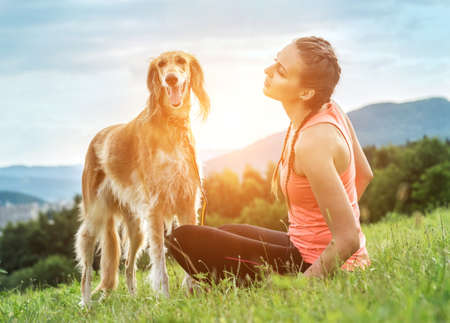 Woman runner and dog on field under golden sunset sky in evening time. Outdoor running. Athletic young man with his dog are running in nature.