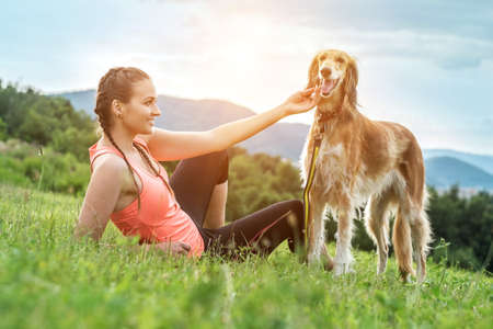 Sports Woman runner and dog on field under golden sunset sky green grass outdoor. Athletic young woman with her in nature. 免版税图像