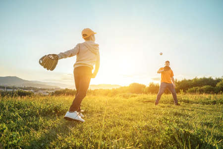Father and son playing in baseball. Playful Man teaching Boy baseballs exercise outdoors in sunny day at public park. Family sports weekend. Father's day. 版權商用圖片
