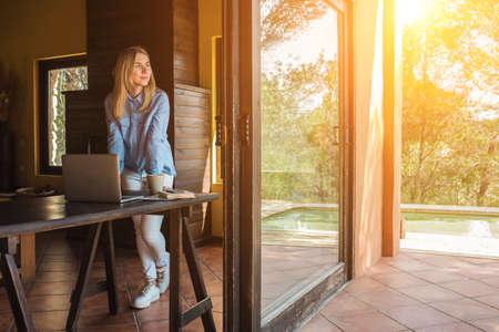 Stay, working at home. Woman drinking tea, spend free time on terrace. Long distance communication. Staying connected, Social distancing. Work life, new reality. 免版税图像