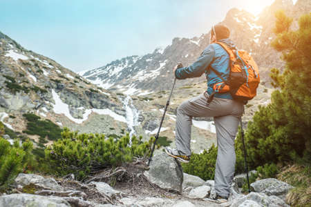 Man hiker, hiking backpacker traveler camper walking on the top of mountain in sunny day under sun light. Beautiful mountain landscape view. Фото со стока