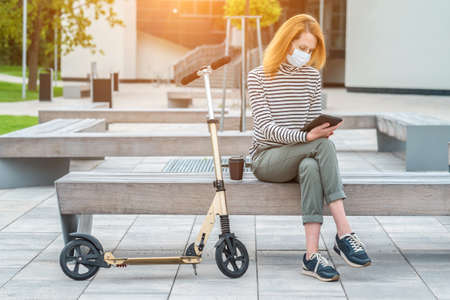 Female wearing masks working over tablet, while sitting on seat in town. Woman face wearing masks. Long distance communication. Staying connected, 4K slow motion video.