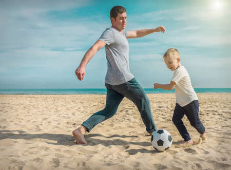 Father and son playing in football on sea coastline beach under sun light in sunny day. Holidays, Sport, Family concept. 免版税图像