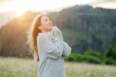Portrait happy woman enjoying sunset stay on the green grass on the forest peak of mountain. Fresh air, Travel, Summer, Fall, Holidays, Journey, Trip, Lifestyle. 免版税图像