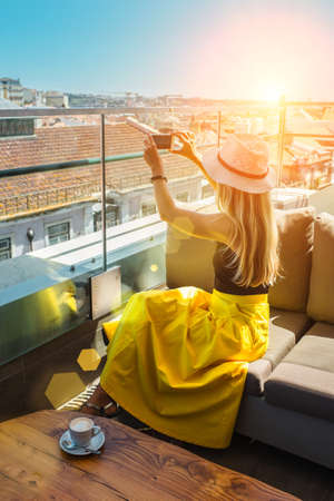 Young traveler woman with smartphone sitting cafe in Lisbon and takes pictures of the city. 免版税图像