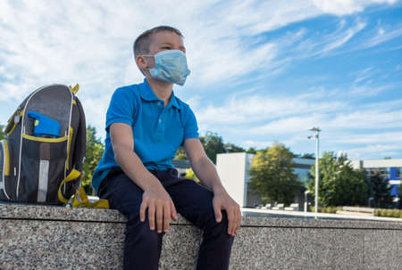 Boy, schoolboy in protective mask sits near the school in sunny September day 免版税图像