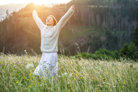 Happy woman enjoying sunset stay on the green grass on the forest peak of mountain. Fresh air, Travel, Summer, Fall, Holidays, Journey, Trip, Lifestyle.