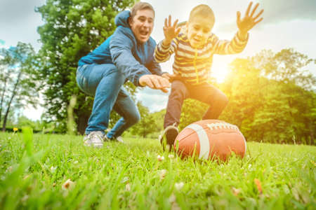 Father and son playing football, Father's day, Playful Man teaching Boy rugby outdoors in sunny day at public park. Family sports weekend. 免版税图像
