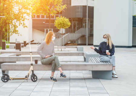 Female colleagues entrepreneurs wearing masks working over tablet, while sitting on seat in town. Woman faces wearing masks. Long distance communication. Staying connected, 4K slow motion video.