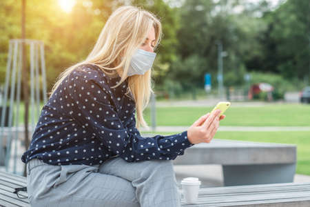 Female wearing masks working over smartphone, while sitting on seat in town. Woman face wearing masks. Long distance communication. Staying connected