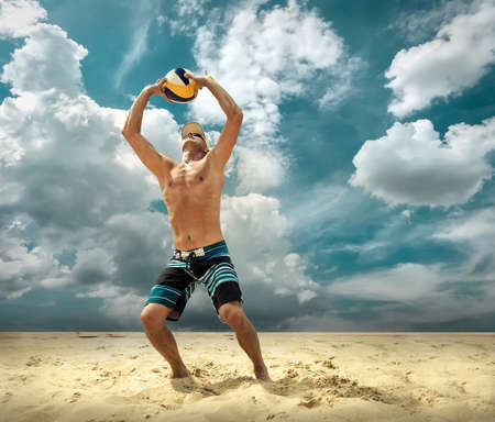 Beach volleyball player in action at sunny day under blue sky. Standard-Bild