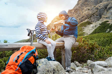 Happy hiker traveler father and son sit on the top of mountain, talking and drink hot tea a thermos. Mountains landscape view. Holidays, fall, travel day.