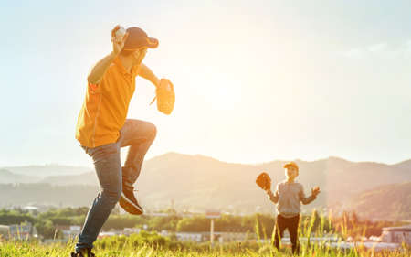 Father and son playing in baseball. Playful Man teaching Boy baseballs exercise outdoors in sunny day at public park. Family sports weekend. Father's day. 免版税图像