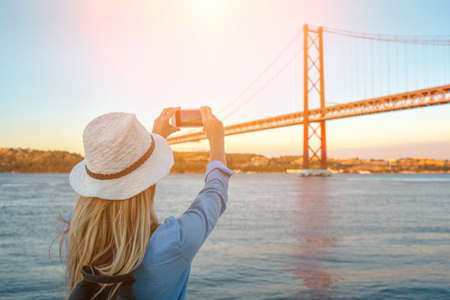 Young traveler woman with smartphone takes pictures in Lisbon of city near the bridge under sunlight in sunny summer day. 免版税图像