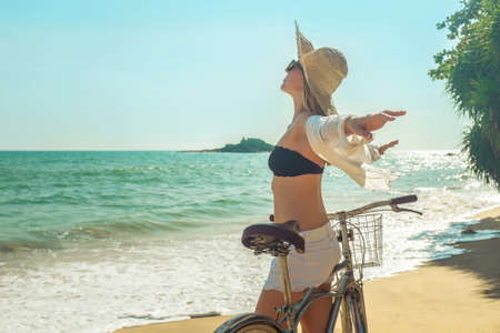 Happiness woman traveler with her bicycle rides on sea coastline and looking on beautifull seascape view in sunny summer day on beach. Freedom, Travell, Journej, concept. 免版税图像