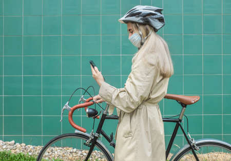 Woman in protective maskin, in helmet using her smartphone device. Female go to work on his sport retro bike. Girl standing on green background. 免版税图像