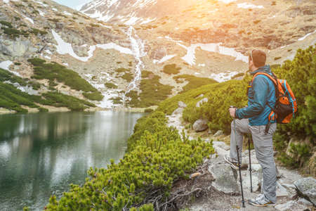 Man hiker, hiking backpacker traveler camper walking on the top of mountain in sunny day under sun light. Beautiful mountain landscape view. 免版税图像