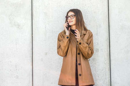 Young girl in glasses speaks by smartphone. student stands on gray background in the street.