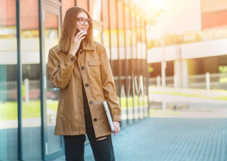 Young girl in glasses talking on smartphone. Woman in the city. Long distance communication. Staying connected. Back to work